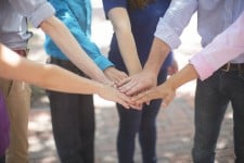 """""""Right Actions"""" about to be taken as a team places their hands onto of each other's to demonstrate unity of progress"""