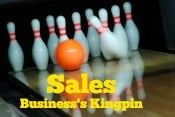 Sales demonstrated as being the kingpin of a business as a orange bowling ball strikes the lead or kingpin in a bowling lane