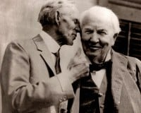 Two elderly men in suits. One whispering to another who is listening and smiling.