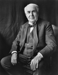 Thomas Edison accomplished in a suit sitting in a chair