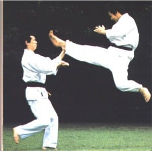 Overcoming obstacles depicted by two men doing karate and one jumping high in the air to execute a blow to the face of the opponent