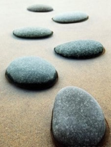 Stepping stones in beach water representing taking right actions toward your success