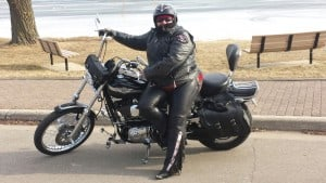 Maggie in full riding gear sitting on motorcycle with ice on lake behind her
