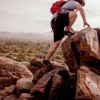 Business Leaders Conquer Fear in 7 Steps depicted with hiker climbing upon a big set of boulders