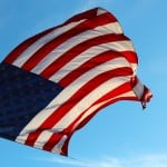Honor depicted with the American flag flying against a blue sky background with a helicopter.