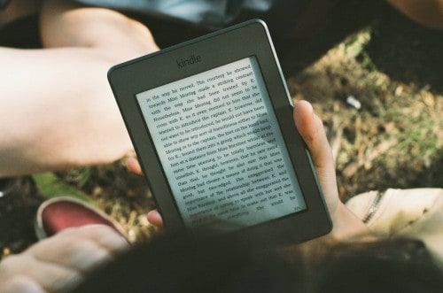 Need a break? Depicted by a couple laying in the grass, under a tree, reading a novel from a tablet.