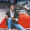 Beverly Hills Cop Movie Poster of Detective Axel Foley holding handgun while sitting on top of a red sports car.