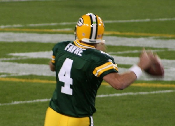 The back of Brett Favre as he is about to pass the football.
