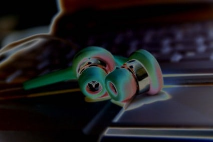 Listening skills depicted by ear buds having neon special effects on them while sitting on a laptop keyboard