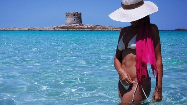 Vacationing depicted by women wearing a white bikini and large hat while standing in the ocean.