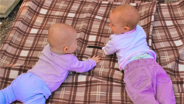 Marketing simplicity depicted by two infants laying on a plaid blanket as they reach out to eachother.