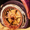 Owning the flaws of business depicted by a flat tire on a rusted out old vehicle.