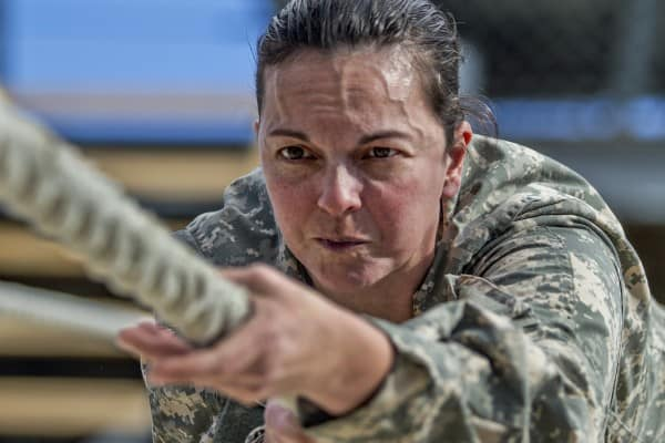 Business Balance depicted by female military personnel crawling across rope with great determination and focus.