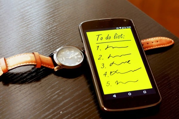 To-Do Lists illustrated by a smartphone with a to-do list on it while it's place along side a watch.
