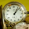 """""""Taking time off"""" before it's too late is illustrated with an antique watch open with the time of 1:08 pm showing. it is upright amidst other antique pocket watches."""