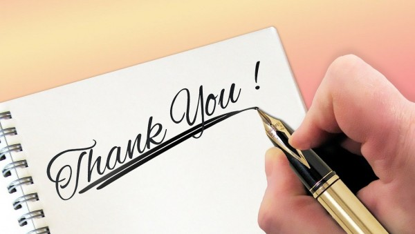 """Thank YOU Cards as trophies illustrated as a man's hand holding a pen and just finished writing """"Thank You!""""."""