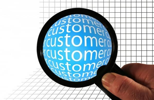 Customer Obsessive illustrated by a magnifying glass being held and magnifying the word customer.