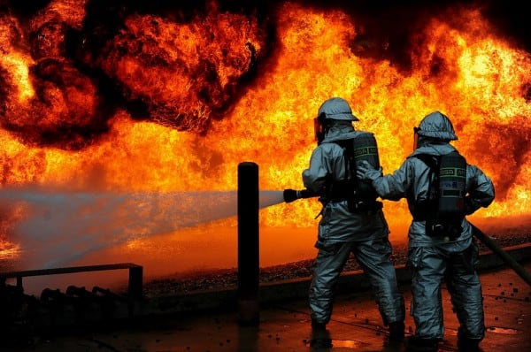Dreaming of being s superhero for your business illustrated by 2 firemen in full suits putting out a blazing fire.