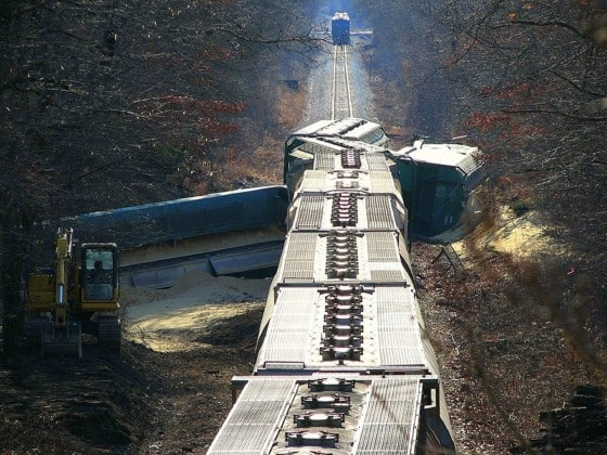 Self sabotaging business success illustrated by a train having several train boxes being derailed in a rural setting.