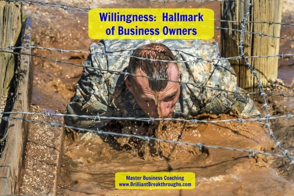 Willingness illustrated by a solider who is in training crawling through the mud to avoid getting cut by the barb wire just above his body.