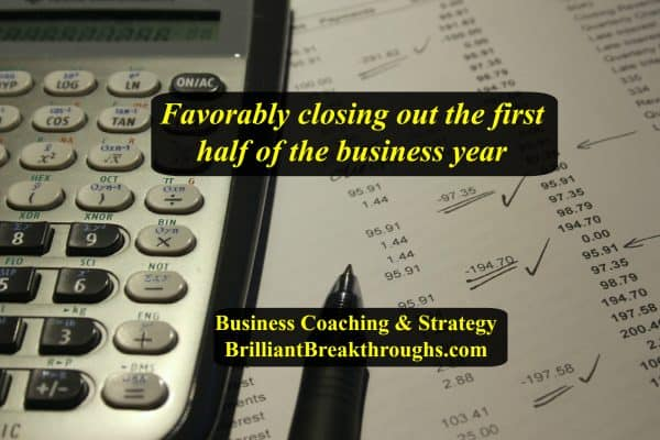 Business Coaching RE: closing out the first half of the business year by Brilliant Breakthroughs, Inc. Illustrated by a calculator and pen going over a report and making corrections.