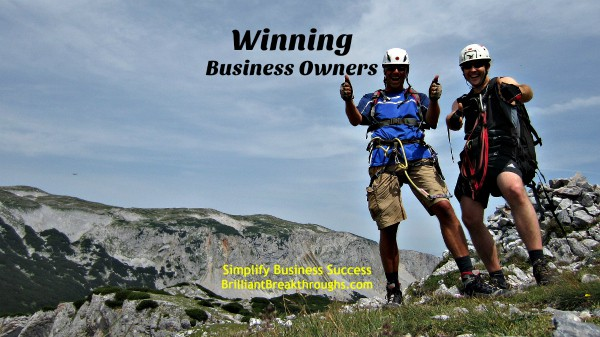 Winning Business Owners illustrated by 2 mountain climbers reaching the summit.