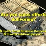Small Business Coaching by Brilliant Breakthroughs, Inc. Topic: Sales efforts illustrated by stacks of dollar bills in a case.