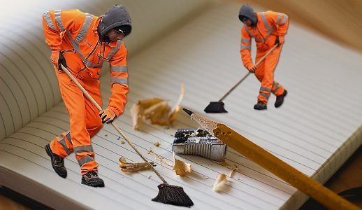 2 men cleaning up a scattered mess with brooms.